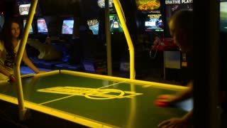 people play air hockey in the amusement park