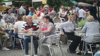 People sit at tables of street cafe - eat and drink beer