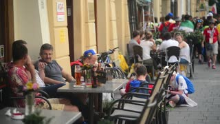 People sitting at street cafe table eating, drinking beer - Krakow Market Square