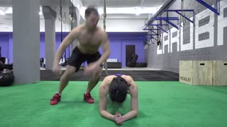 People Training In Crossfit Gym. Jumping over a girl.