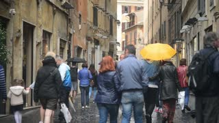People walk through the narrow streets of Rome Italy