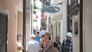 People walking down The narrow streets of the old Italian town