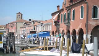 Pier on the waterfront of Murano island in Venice - people and shops