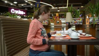 Pregnant woman eating cake at the mall cafe