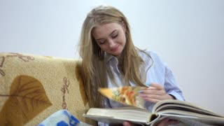 Pretty Blonde Woman Reading A Recipe in Italian Cuisine Cooking Book