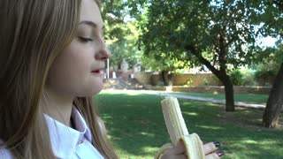 Pretty young Blonde Girl eating a Banana in the City Park