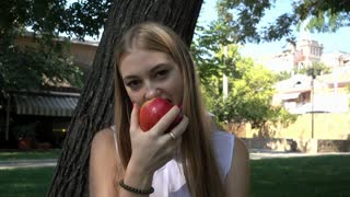 Pretty young Blonde Girl eating a juicy red Apple in the Park