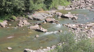 river with rapids and rocks in the mountains - people sunbathe on a rock