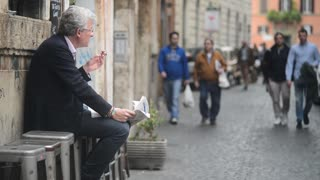Rome, Italy. Elderly man reading a newspaper on the street