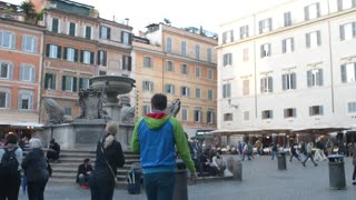 Rome, Italy. Fountaine on piazza Trastevere. Tourists relax, eating, walking.