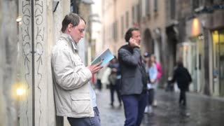 Rome, Italy. Young man reading a book on the street