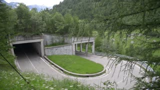 Serpentine mountain road and tunnel in the Alps