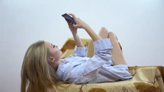 Sexy Young Woman Lying In Sofa And Chatting Sending Sms with Mobile Phone