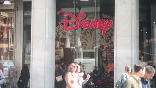 Shopping in Milan, Disney sign above the entrance to the store people enter