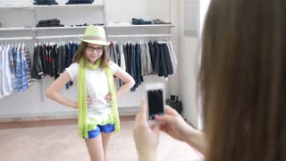 Shopping Mother makes Photo of Daughter using a Mobile Phone in a Clothing Store