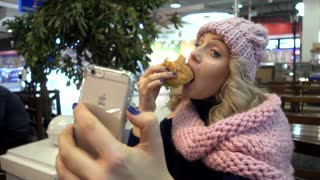 Smiling Woman Blonde Eating Burger in Mall Fast Food Cafe and takes Selfie Photo
