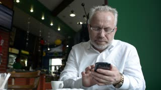 Solid business Man talking on a Cell Mobile Phone sitting in a cafe