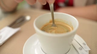 stirring the sugar in a cup of coffee