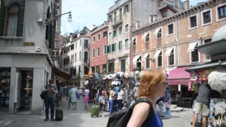 streets and canals of Venice. People walk along the cafes and souvenir shops