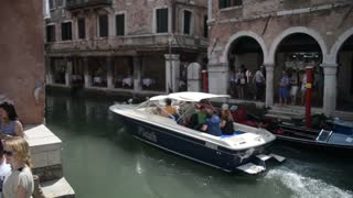 Summer in the streets and canals of Venice. Boat is sailing on the water