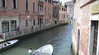 Summer in the streets and canals of Venice. Boats are sailing on the water
