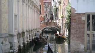 Summer in the streets and canals of Venice. The gondola is sailing on the water