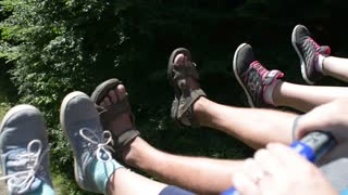 Swinging feet on Cable car, chair lift pulls tourists up the green mountain