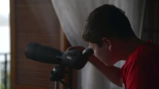 The boy looking in a telescope through the window at sea