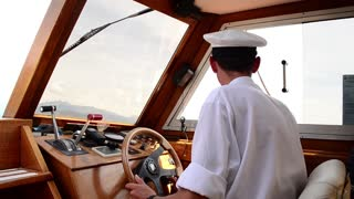 The captain controls of the boat, turn the steering wheel