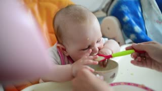 The child eagerly eating baby food with spoon