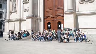 the crowd sitting on the steps of the Museum of San Fedele, Milan