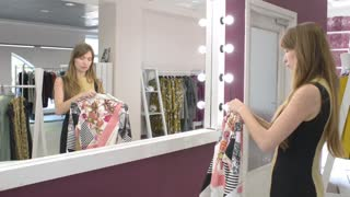 The girl tries on a jacket dress before a mirror in a boutique
