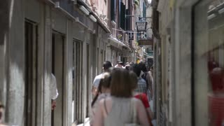 The narrow street in Venice. Tourists go to the waterfront