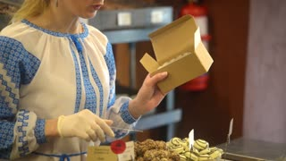 The seller in the candy store shop puts chocolates in a box - Lvov, Ukraine