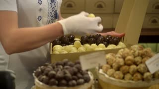 The seller in the candy store shop puts chocolates off a box - Lvov, Ukraine