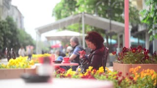 The woman at the coffee shop with a mobile phone