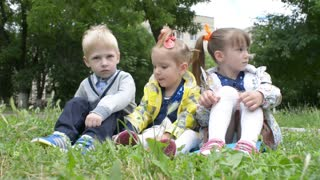 Three children sitting on the grass - a picnic in the park