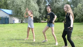 Three girls dancing fun in the summer park on the green grass