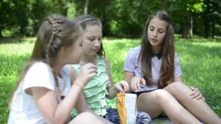 Three girls eat potato chips on a picnic in the park