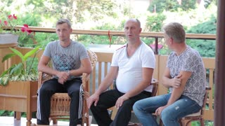 Three middle-aged men talking, have a rest on the terrace pension