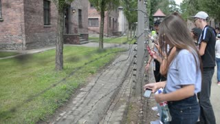Tourists in Auschwitz Concentration Camp - barracks and barbed wire