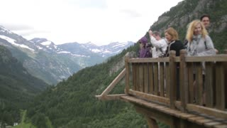 Tourists taking photo on viewing platform in the Alps