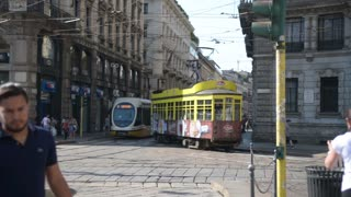 Trams and people on the streets of central Milan