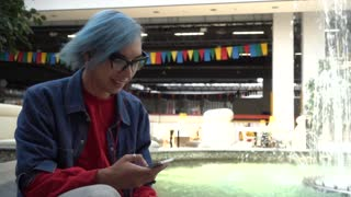 Transgender Gay with blue Hair sitting chating with Mobile Phone in Mall