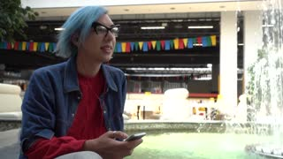 Transgender Gay with blue Hair sitting listening to music through headphones