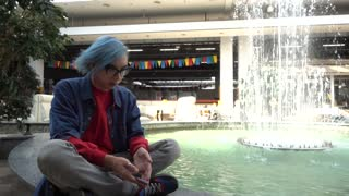 Transgender Gay with blue Hair sitting sadly alone - Mobile Phone in Hand chatin