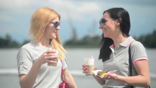 Two beautiful girls drink coffee  - paper cup - standing at the river