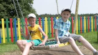 Two boys ride on a swing in the park playground