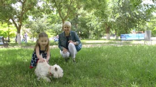 Two girls and a white dog sitting on the grass secretive - a picnic in the park