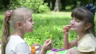 Two girls eat potato chips on a picnic in the park
